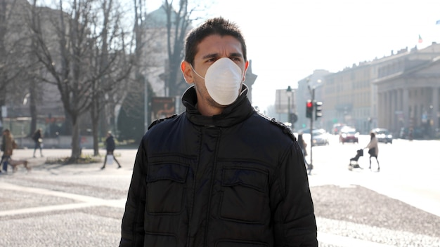 Covid-19病気のウイルスの拡散を防ぐフェイスマスクを身に着けている街の通りの男:コロナウイルス病2019。 Premium写真