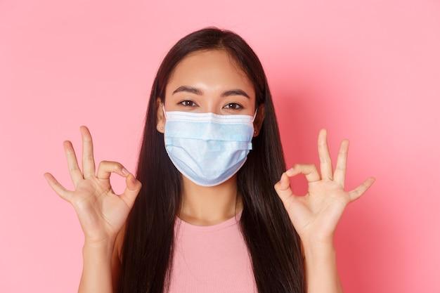 Пандемия covid-19, коронавирус и концепция социального дистанцирования. крупным планом взволнованная и пораженная симпатичная азиатская девушка хвалит отличный выбор, хорошо выполненную или хорошую работу жестом, показывает все в порядке и надевает медицинскую маску Бесплатные Фотографии