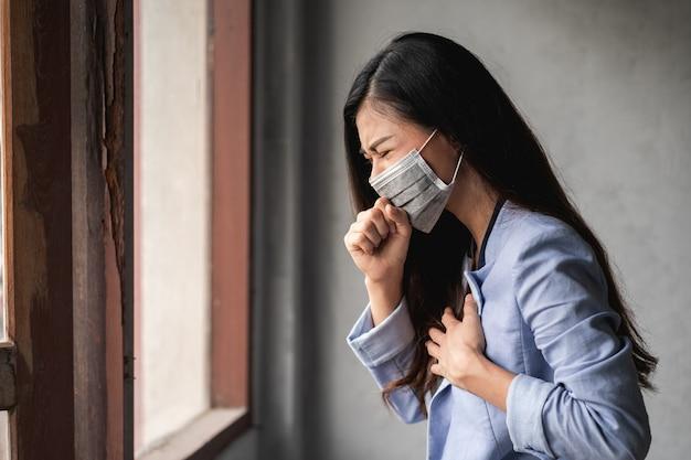 Covid-19パンデミックコロナウイルス、マスクを身に着けているアジアの女性、咳と発熱の症状があります Premium写真