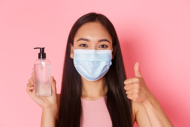 Covid-19 pandemic, coronavirus and social distancing concept. satisfied, cheerful asian pretty girl in medical mask, recommend antiseptic, show thumbs-up while showing hand sanitizer, pink wall Free Photo