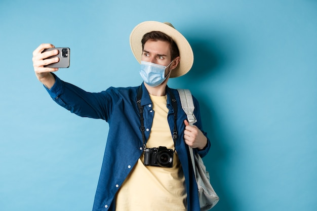 Covid-19, pandemic and travel concept. tourist on summer vacation taking selfie in medical mask, photographing on smartphone, standing on blue background. Premium Photo