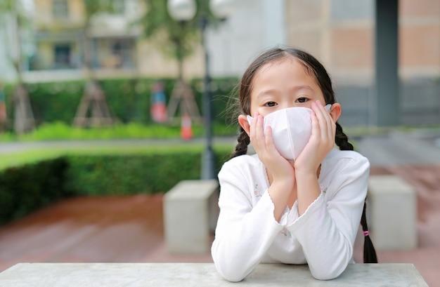 コロナウイルスcovid-19とマスクの概念による汚染防止。タイのバンコク市でコロナウイルスと大気汚染pm2.5を保護するためにマスクを着ているアジアの小さな子供の女の子の肖像画。 Premium写真