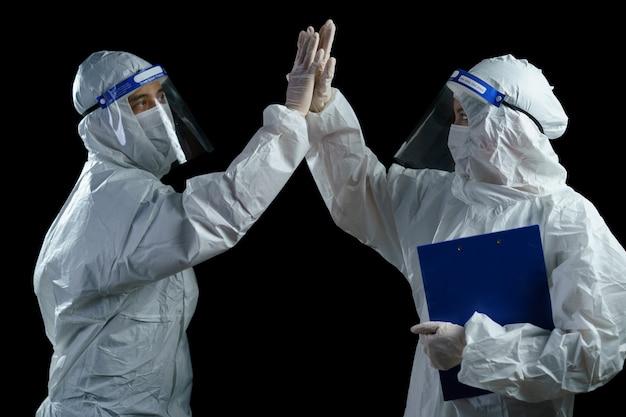 Covid-19の発生を阻止するために祝っているppeと顔面シールドを装着した医師。 Premium写真