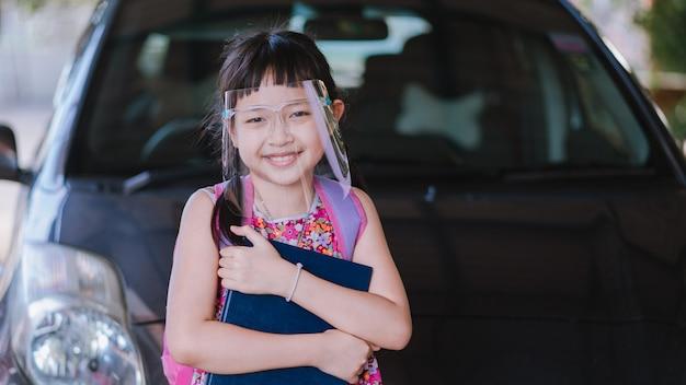 Covid-19 quarantine.16:9のスタイルの後、学校に戻っているときに顔のシールドを身に着けている少女の笑顔 Premium写真