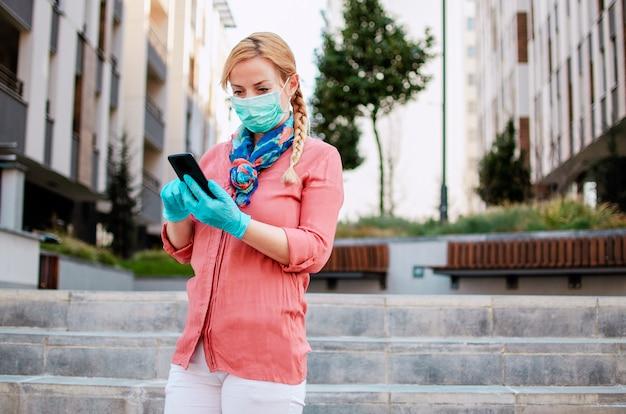 Женщина носит защитную медицинскую одежду, используя мобильный телефон, прогуливаясь по улице города во время вируса covid-19. ответственное поведение при пандемии короны. женщина отправляет sms-сообщения на телефоне с латексными перчатками Premium Фотографии