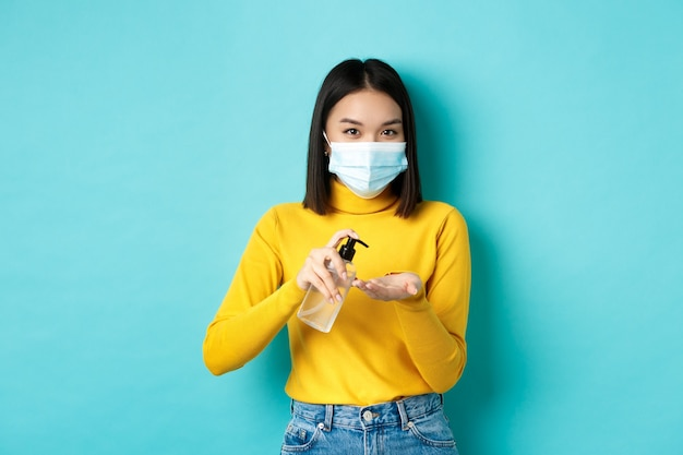 Covid-19, социальное дистанцирование и концепция пандемии. улыбающаяся азиатская женщина в медицинской маске, использующая профилактические меры от коронавируса, используя дезинфицирующее средство для рук, стоя на синем фоне. Premium Фотографии