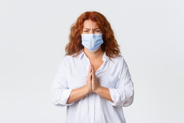 Социальное дистанцирование covid-19, меры профилактики коронавируса и концепция людей. обнадеживающая взволнованная женщина средних лет в медицинской маске, женщина с рыжими волосами, умоляющая о помощи, умоляющая об одолжении. Бесплатные Фотографии