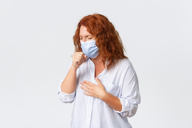 Distanziamento sociale covid-19, auto-quarantena del coronavirus e concetto di persone. donna rossa di mezza età malata che tossisce, indossa una maschera medica, ha la gola acida, i sintomi della malattia, ha contratto l'influenza. Foto Gratuite