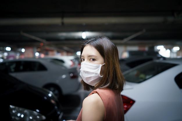 Распространение covid-19. женщина в медицинской защитной маске на стоянке. страх коронавируса. Premium Фотографии