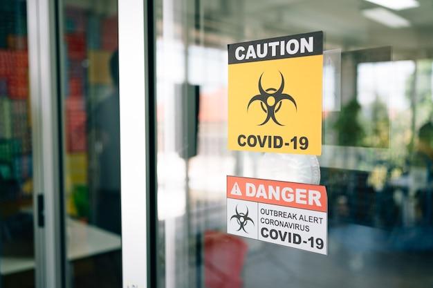 Covid-19 경고 표지판이 유리문에 붙어 있습니다. 코로나 바이러스의 검역 및 발생 경보 징후. 프리미엄 사진