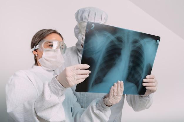 医師はクリニックでcovid-19患者の肺炎のx線検査を行います。コロナウイルスの概念。 Premium写真