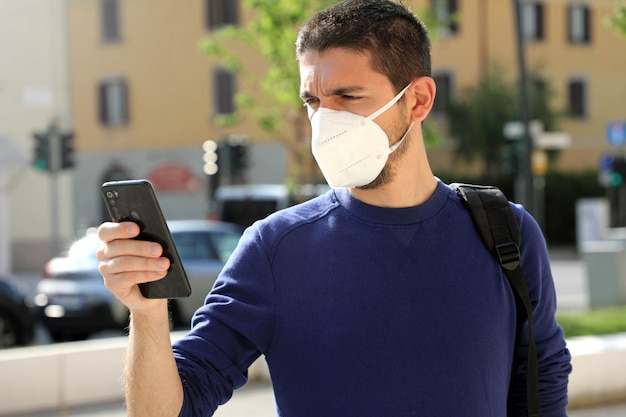 Covid-19 young man wearing ffp2 mask using smart phone in city street Premium Photo