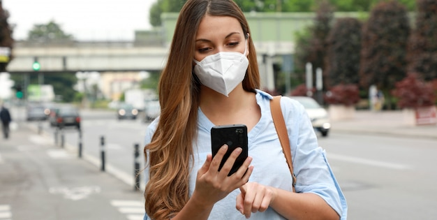Covid-19 young woman wearing ffp2 mask using smart phone in city street Premium Photo