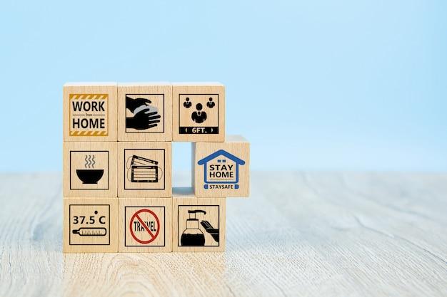 Пребывание дома и значок предупреждения covid-19 на деревянном игрушечном блоке. Premium Фотографии