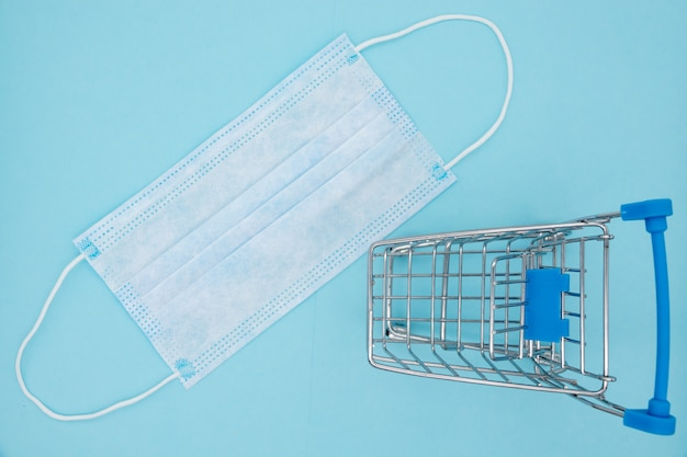 Маска и тележка на синем фоне, покупки для защиты covid-19. Premium Фотографии
