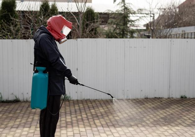 制服を着た男性と防毒マスク、スプレーガンを使用して通りを消毒剤で処理する予防策コロナウイルスcovid-19 Premium写真