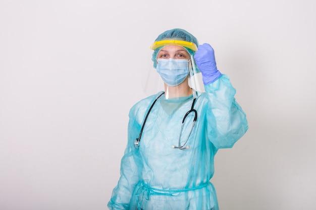 医師、看護師、白い背景のcovid-19コロナウイルスとの戦闘用保護スーツを着ています。コロナウイルスの発生と戦うために彼女のこぶしを持ち上げる顔面シールド付き防護服の医療従事者 Premium写真