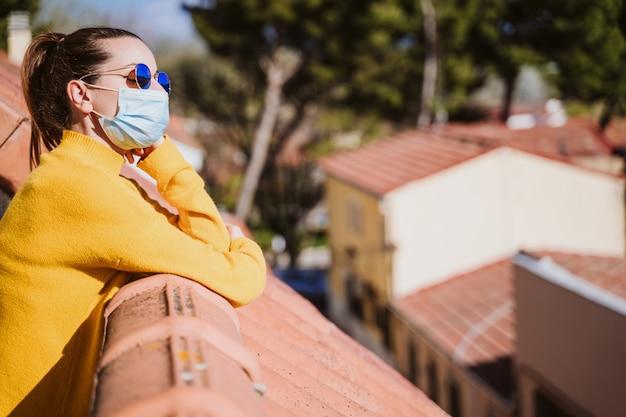 防護マスクを着用し、晴れた日を楽しんでいるテラスで自宅で若い女性。コロナウイルスcovid-19コンセプト Premium写真