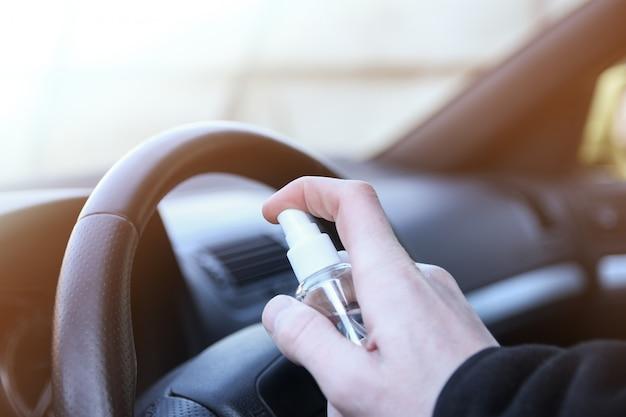 車内を洗浄し、消毒液を噴霧します。車のハンドルとハンドルの消毒。コロナウイルス、covid-19保護。車内の消毒、 Premium写真
