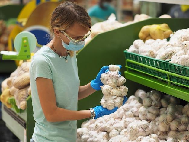 パンデミックコロナウイルスcovid-19の期間中に食料品店でニンニクを選択する青い手袋とフェイスマスクの女性。 Premium写真
