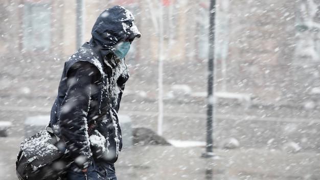 Молодой человек в темной одежде и медицинском для защиты от маски covid-19 движется по заснеженной улице Premium Фотографии