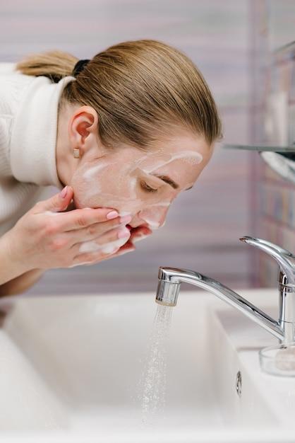 コロナウイロス防止。抗菌性石鹸と流し台の流水で顔を洗ってください。洗顔。流行性のcovid-19。コロナウイルス予防の身体衛生。インフルエンザの病気。 Premium写真