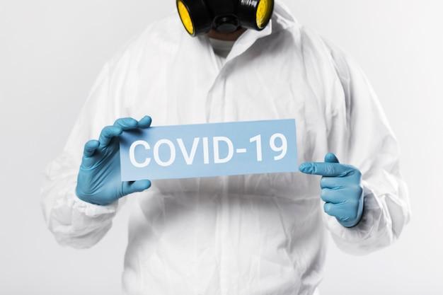 Мужчина держит карточку covid-19, вид спереди Бесплатные Фотографии