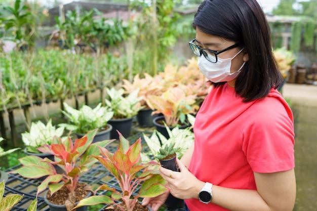 Новая нормальная азиатская красавица носите маску для предотвращения covid 19 или коронавируса. выберите дерево, чтобы украсить дом Premium Фотографии