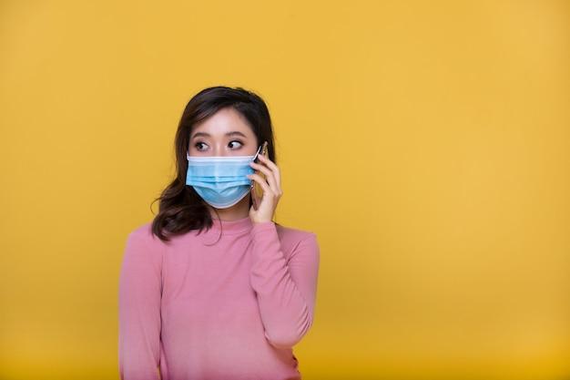 Портрет азиатская красивая счастливая молодая женщина, носящая маску или защитную маску от коронавирусного кризиса или вспышки covid-19, и она использует мобильный телефон или смартфон на желтом фоне Premium Фотографии