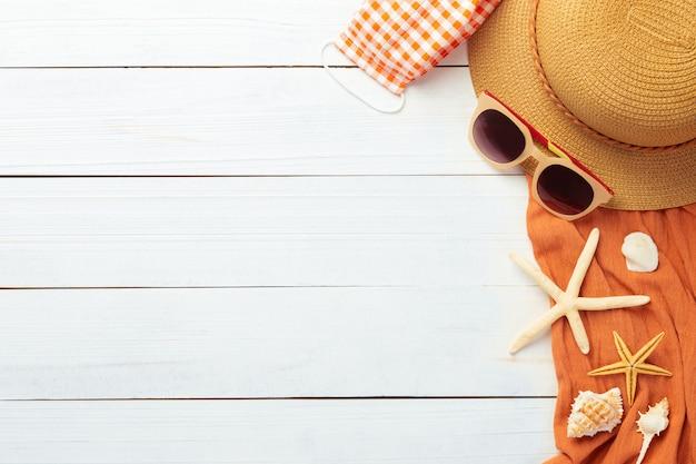ビーチアクセサリー-麦わら帽子、サングラス、タオル、covid-19を防ぐためのマスクと夏の背景 Premium写真