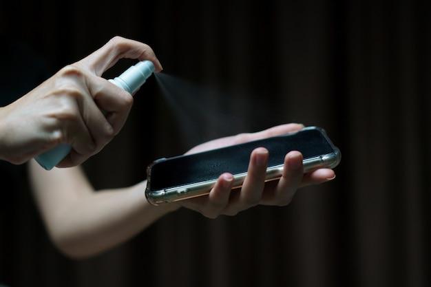 コロナウイルスまたはcovid-19保護用のイソプロピルアルコールスプレーで携帯電話の画面を手で持って掃除します。 Premium写真