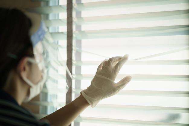 窓のブラインドを通して見る保護医療スクリーンまたはプラスチック製の顔面シールドを身に着けている女性。コロナウイルスまたはcovid-19保護用 Premium写真