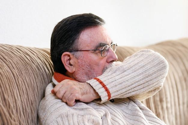 Пожилые люди чихают, кашляя в ее рукав или локоть, чтобы предотвратить распространение covid-19. вирус короны, у больного старшего человека грипп, чихание покрывает нос, рот рукой. Premium Фотографии