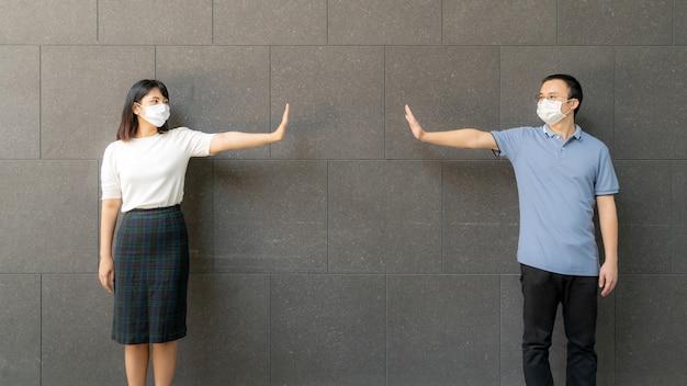 Молодые азиатские пары нося маски встречи и стоя у стены внутри на открытом воздухе для социального дистанцирования для риска инфекции и предотвращения заболевания covid-19. Premium Фотографии