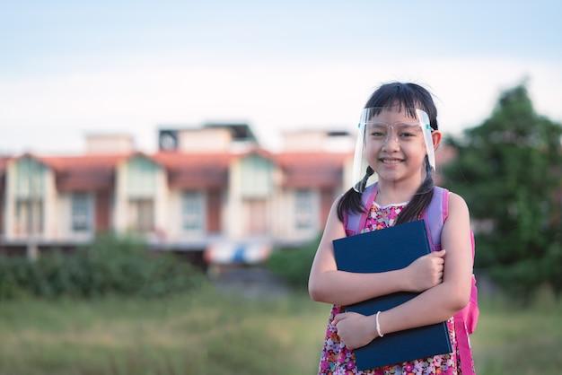 Covid-19の検疫後、学校に戻っているときに顔面シールドを身に着けている少女の笑顔。 Premium写真