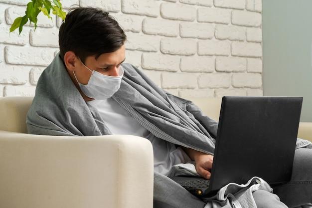 コロナウイルスの間に家にいる白人男性/医療用マスクを身に着けているcovid-19検疫 Premium写真