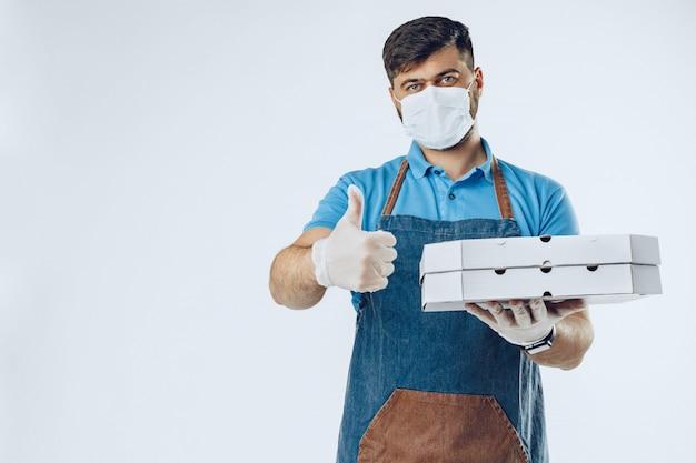 医療用手袋とマスクのピザ配達人。コロナウイルスcovid-19発生中の安全なサービス Premium写真