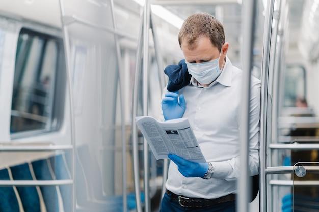 Пандемия коронавируса, covid-19, карантинная мера. серьезный взрослый мужчина в белой рубашке, держит черный пиджак, сосредоточен в газете, носит защитную маску и перчатки, позирует в вагоне метро Premium Фотографии