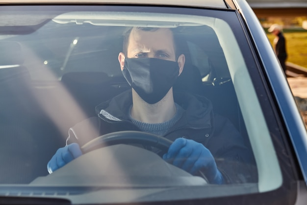 Covid-19コンセプト。男は青い保護医療用手袋と黒いマスクで車を運転します。細菌やウイルスからの保護。コロナウイルス防止。保証とコロナ病。 Premium写真