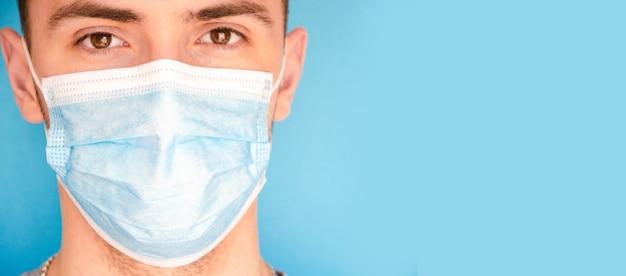 Человек в синей медицинской маске на синем фоне, боком. место для текста. копировать пространство. covid-19 Premium Фотографии