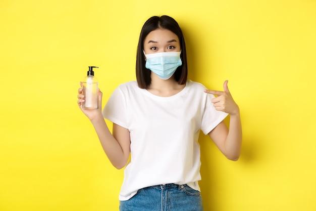 Covid, здравоохранение и концепция пандемии. азиатская девушка в маске от коронавируса, указывая пальцем на хорошее дезинфицирующее средство для рук, стоит на желтом фоне. Premium Фотографии