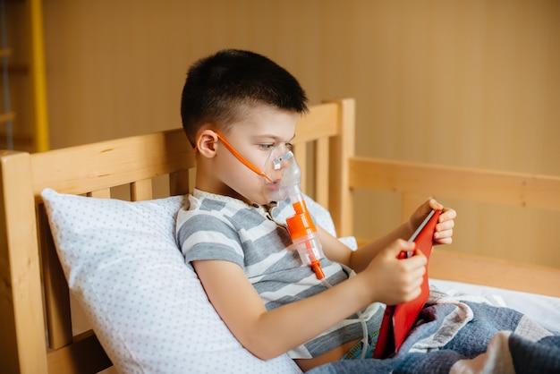 少年は、肺の吸入処置中にタブレットで遊ぶ。 covid19、コロナウイルス、パンデミック。 Premium写真