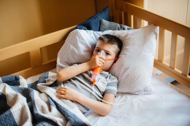 Молодому мальчику делают ингаляцию при заболевании легких. covid19, коронавирус, пандемия. Premium Фотографии