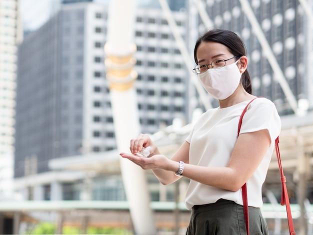 Красивые азиатские женщины, носящие медицинскую маску для лица, используют спиртовой гель или дезинфицирующее средство для очистки рук, находясь в общественных местах или в центре города, как новая нормальная тенденция и самозащита от инфекции covid19 Premium Фотографии