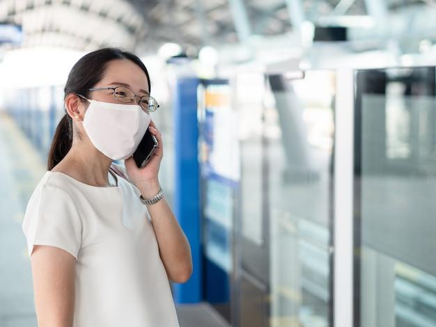 Красивые азиатские женщины носят одноразовые медицинские маски, используя смартфон во время ожидания метро на платформе вокзала, как новый нормальный тренд и самозащиту от инфекции covid19. Premium Фотографии
