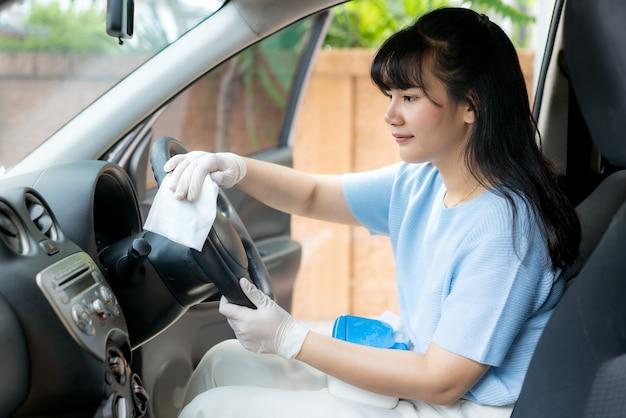 ボックスから消毒剤の使い捨てワイプで車のステアリングホイールを消毒するアジアの女性。ウイルスやバクテリアを防ぐ、covid19、コロナウイルスを防ぐ、 Premium写真