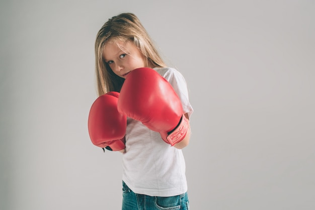 Cowardly funny young girl in red boxing gloves Premium Photo