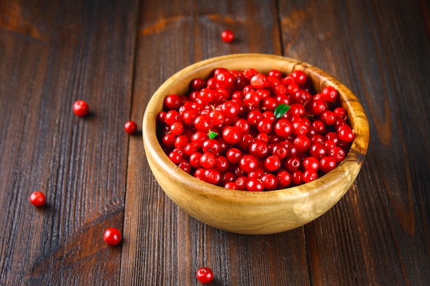 Cowberry, foxberry, cranberry, lingonberry in a wooden bowl on a brown wooden table. Premium Photo