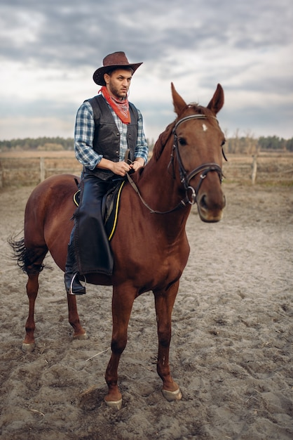 Ковбой в кожаной одежде верхом на лошади на ферме Premium Фотографии