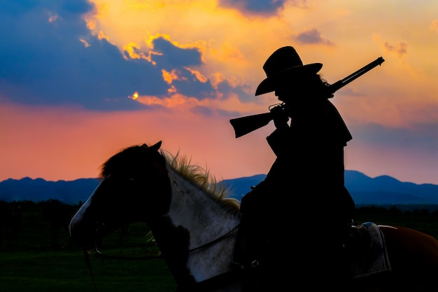 Cowboy silhouette on a horse during nice sunset Premium Photo